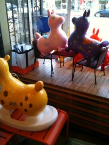 Rody sits on woven plastic chairs in the window of Plastica