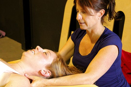 A masseuse worked the weary shoulders of bicyclists.
