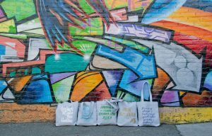 Artecnica Tote bags in front of graffiti